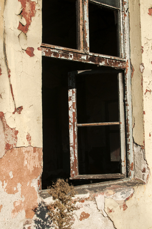 crumbling: Crumbling wall of abandoned grunge building with broken window Stock Photo