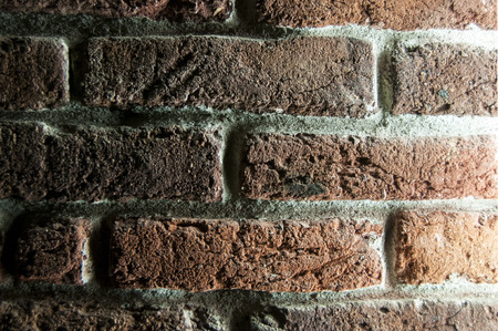side lighting: Brick wall illuminated with side artificial lighting closeup as background Stock Photo