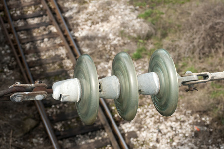 the insulator: High-voltage ceramic insulator on railway tracks background Stock Photo