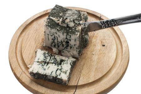 白い背景に分離された木製のトレイの白チーズとナイフのカビの塊をスライス