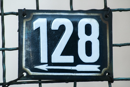 enameled: Weathered grunge square metal enameled plate of number of street address with number 128 closeup