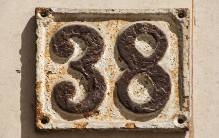 38: Old retro weathered cast iron plate with number 38 Stock Photo