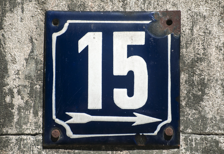 number 15: Weathered grunge square metal enameled plate of number of street address with number 15 closeup Stock Photo