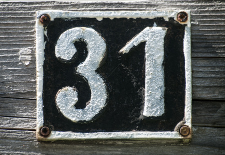 31: Old retro weathered cast iron plate with number 31