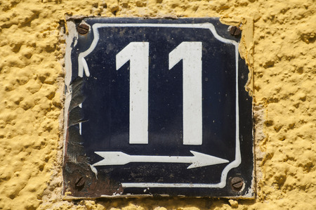 enameled: Weathered grunge square metal enameled plate of number of street address with number 11 closeup