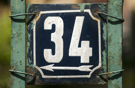 34: Old retro weathered cast iron plate with number 34