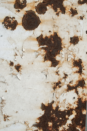 corroding: Old weathered metal surface painted with cracked white paint and rust stains closeup as background