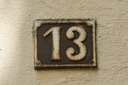 13: Old retro weathered cast iron plate with number 13 Stock Photo