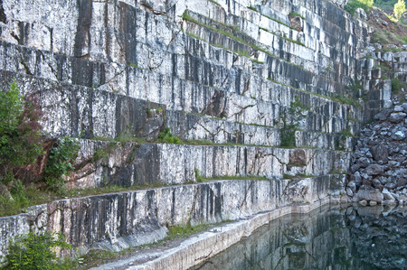 abandonment: Overlooking the wall of abandoned marble quarry and pond Stock Photo
