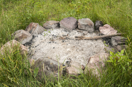 the ashes: Unlit camp fireplace with ashes and stones on mountain meadow