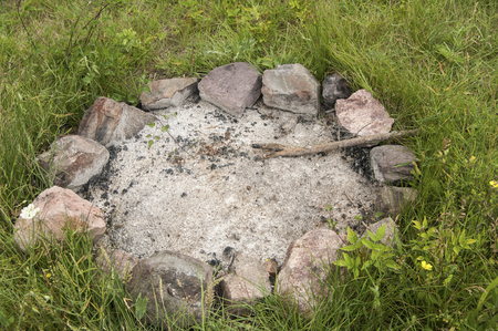 unlit: Unlit camp fireplace with ashes and stones on mountain meadow