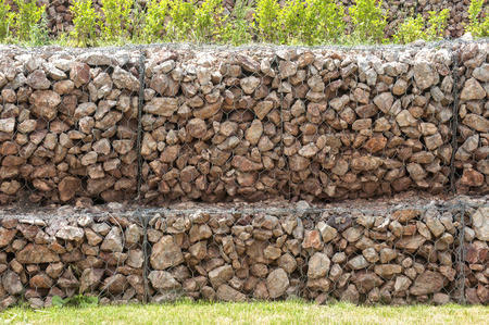 gabion mesh: Hexagonal wire netting gabion box wall filled with stones closeup as background