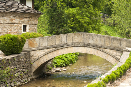 the vaulted: Old stone country house and stone vaulted bridge over small river