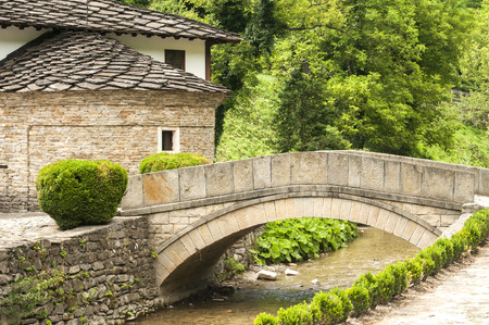 Old stone country house and stone vaulted bridge over small river