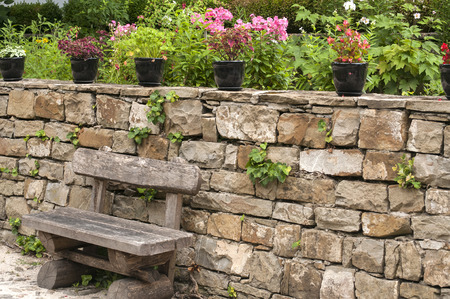 Wooden bench in front of stone wall and pots of flowers