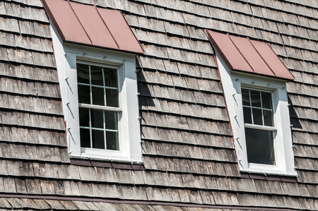 attic: Two attic windows of pointed wooden roof of old house