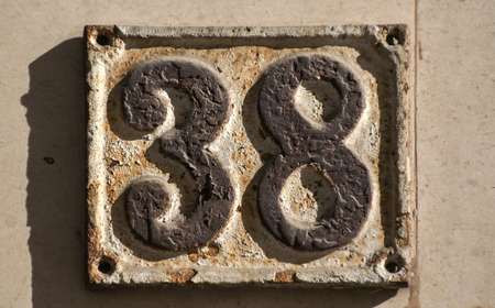Old retro weathered cast iron plate with number 38 Stock Photo