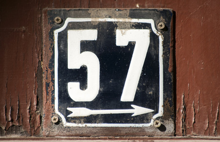 enameled: Weathered grunge square metal enameled plate of number of street address with number 57 closeup Stock Photo