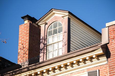 attic window: Attic window and chimney closeup on vintage red brick building top