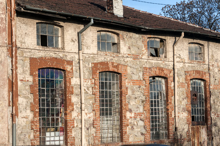 urban decay: Glass iron windows of old grunge abandoned vintage industrial building