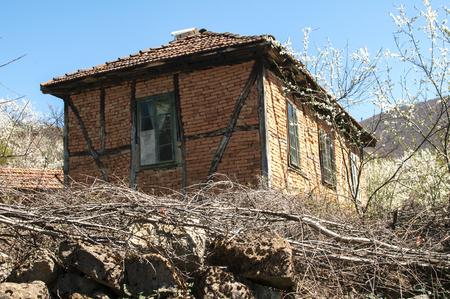 Old non plastered brick desolate frame-build rural farmhouse behind run-down stone wall