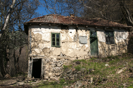 Old abandoned grunge rural country house in springtime mountain