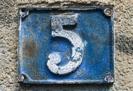 Old retro weathered cast iron plate with number 5 closeup Stock Photo