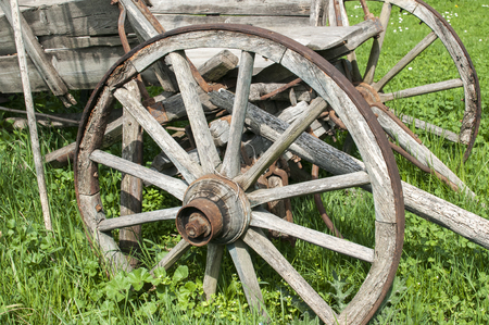 Wooden wheels on old rural weathered cart on green grass meadow Stock Photo