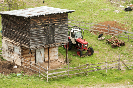 Farm garden with wooden shed and vintage tractor Stock Photo