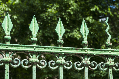 Old vintage retro green painted iron fence ornaments closeup