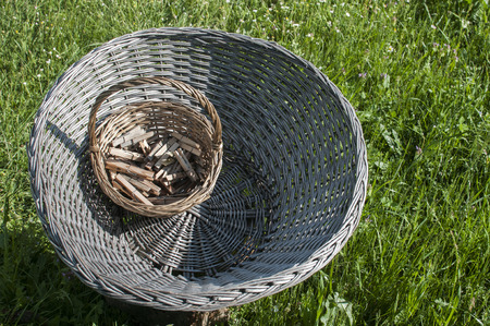 log basket: Big old weathered empty wicker laundry basket and small basket full of wooden clothes pegs on wooden log on green grass country garden meadow Stock Photo