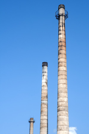 desolacion: Abandoned and crumbling vintage obsolete industrial chimneys on blue sky background Foto de archivo