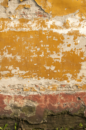 Old vintage grunge brick wall surface with crumbling plaster closeup as background