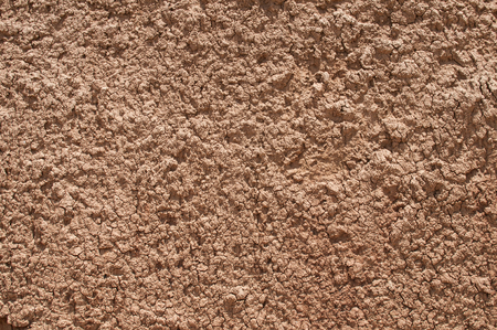 Red clay soil closeup as natural background