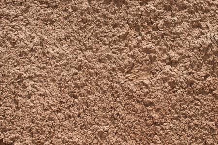Sol argileux rouge closeup comme fond naturel