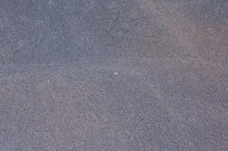 灰色の黒の細かい海のビーチの砂の粒は、背景としてクローズアップ 写真素材