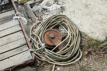 Old rusty weathered iron reel with used wound rope on grunge background Stock Photo