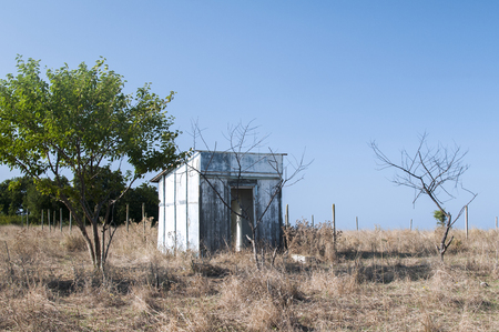 Abandoned and demolished wooden bungalow on terrain with dry grass in summertime