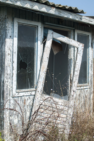 Abandoned and demolished wooden bungalow in summertime