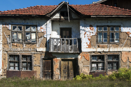 Old abandoned decayed grunge rural rickety house clay crumbled facade with neglected wooden windows, balcony and doors