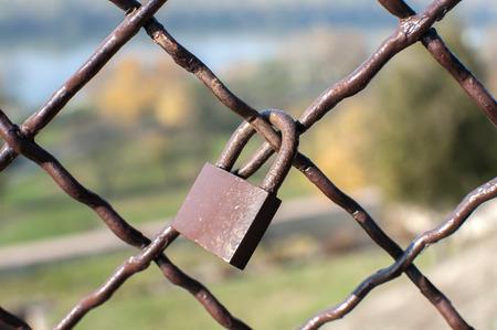 Metal padlock locked on weathered vintage metal mesh closeup
