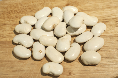 A pile of big white dry navy beans closeup on wooden board