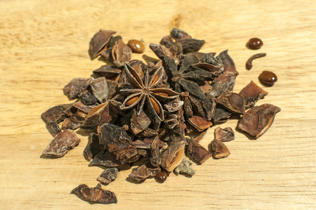 A pile of broken star anise seed as spice closeup on wooden board background