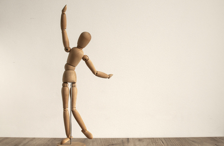 Wooden dummy toy poses on white wall background Stock Photo
