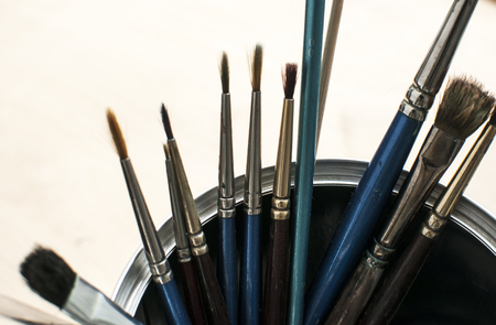 A bunch of different types of paint brushes placed in a can on white background