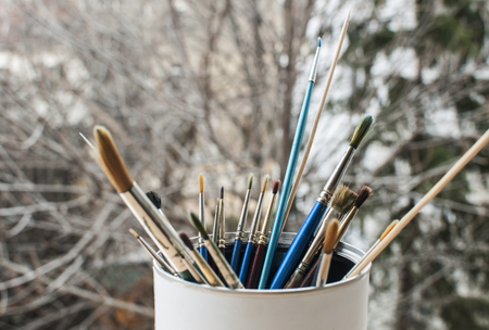 A bunch of different types of paint brushes placed in a can on tree branches background Stock Photo