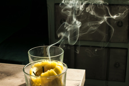 White smoke from recently extinguished candle on home interior background