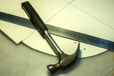 Hammer, metal ruler and cardboard cuts as tools in workshop production of leather goods