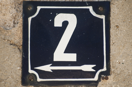 Weathered grunge square metal enameled plate of number of street address with number 2 closeup