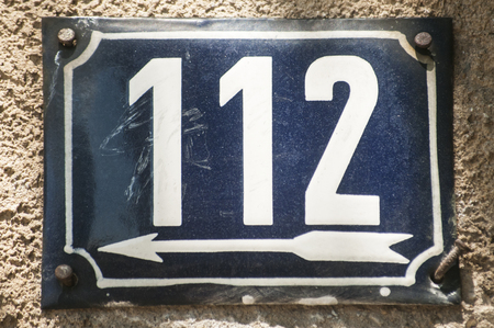 Weathered grunge square metal enameled plate of number of street address with number 112 closeup